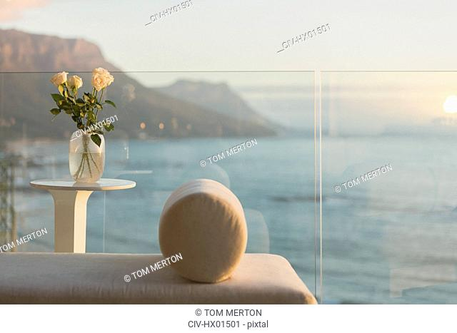 Tranquil ocean view from luxury balcony with chaise lounge and rose bouquet