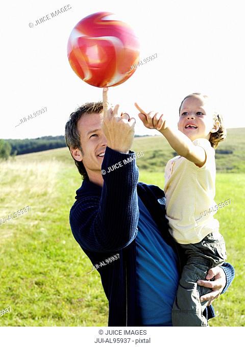 Father and daughter playing with ball in park