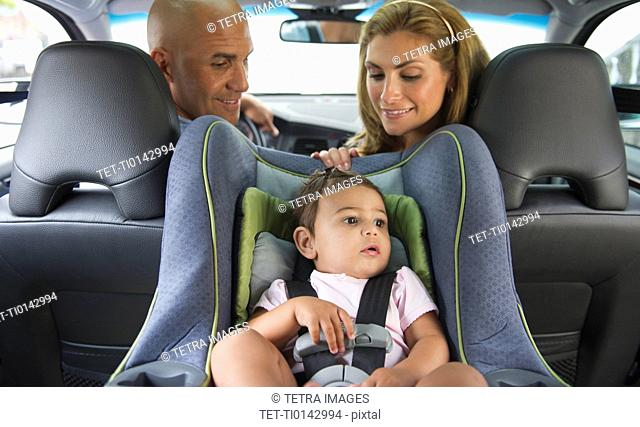 Young family with small girl 12-18 months sitting in car