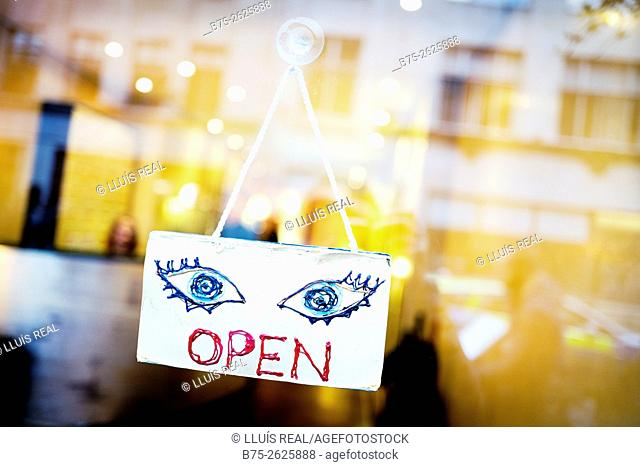 A sign hanging on the glass door of a business, with reflections of the buildings, OPEN with the text and drawn two eyes, London, England, UK, Europe