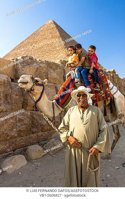 Camel driver with children by the Great Pyramid. Cairo, Egypt