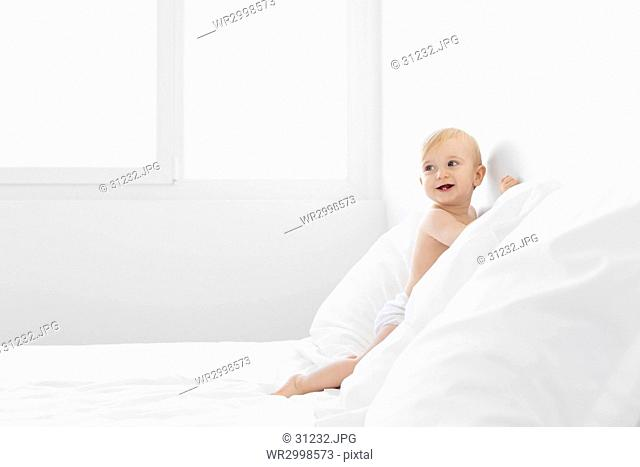 Baby boy with blond hair leaning on a bed with white duvet and pillows