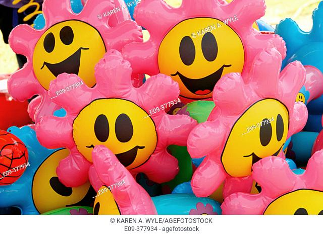 Pink and yellow flower smiley-face balloons at carnival booth at county fair, Monroe County, Indiana, USA