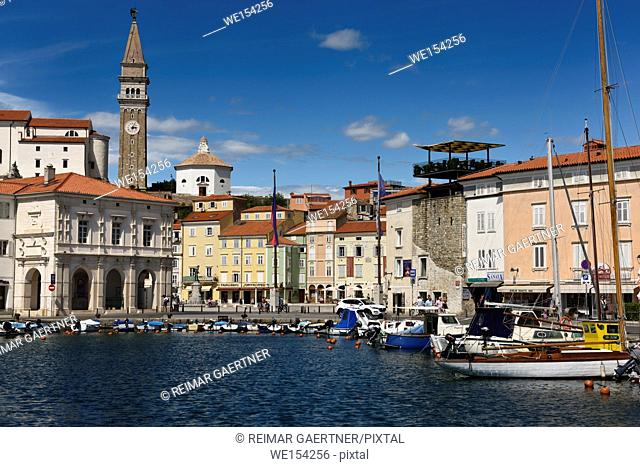 Piran Slovenia with inner harbor lined with boats and Tartini Square with St George's Cathedral with St Marks Venice belfry replica