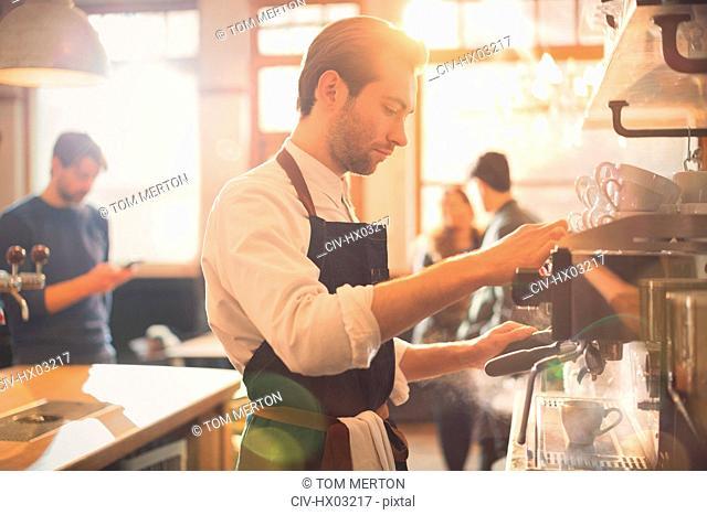 Male barista using espresso machine in cafe