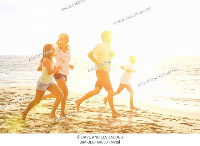 Caucasian family running on beach