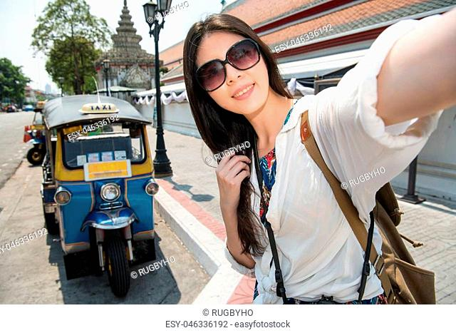 Travel selfie smart phone by woman in bangkok, thailand. Happy smiling asian girl taking self portrait photo standing on street near Wat Pho and tuk tuk car