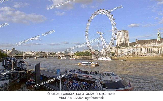 Tourist boat travels along the River Thames at Westminster with the London Eye in the background