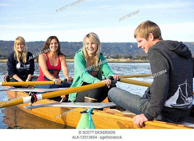 Young adults rowing in a canoe, South-central Alaska; Homer, Alaska, United States of America