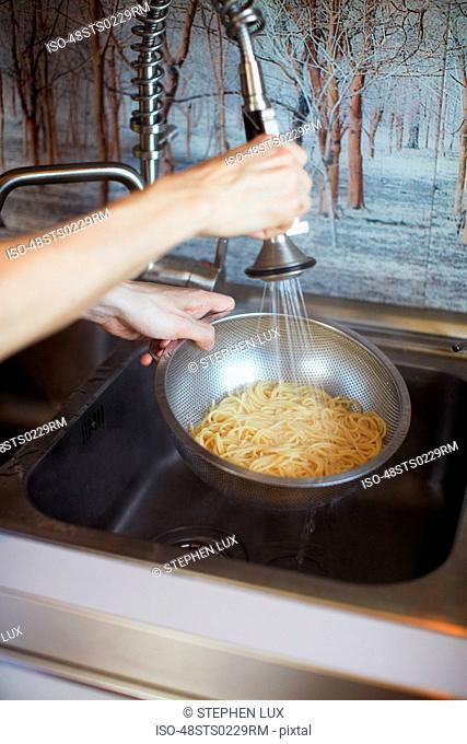 Hands rinsing pasta in sink