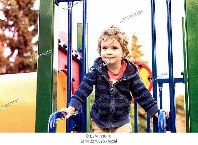 Toddler boy playing at a city playground at sunset; St. Albert, Alberta, Canada