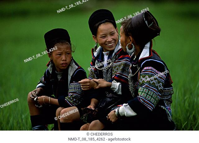 Side profile of three young women sitting in a field and talking, Vietnam