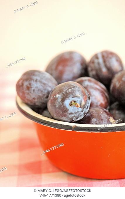 Plums in a red metal bowl  Fresh purple plums in an enamel red bowl on red gingham cloth