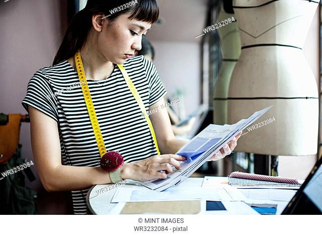 Japanese female fashion designer working in her studio, looking at fabric samples