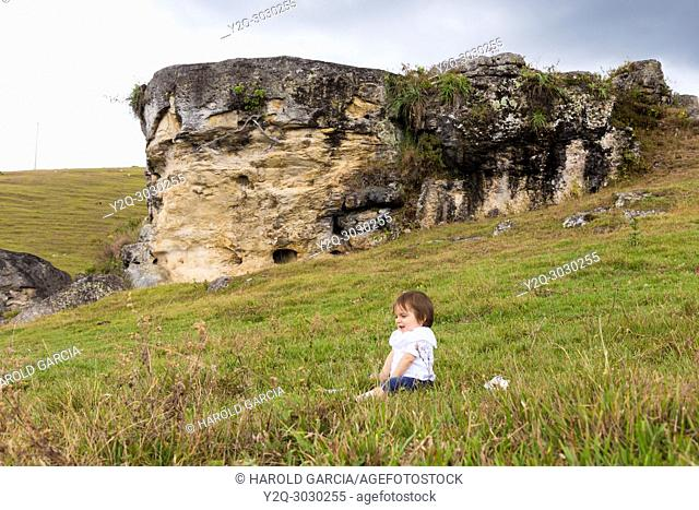 Baby sitting in the grass next to a big rock