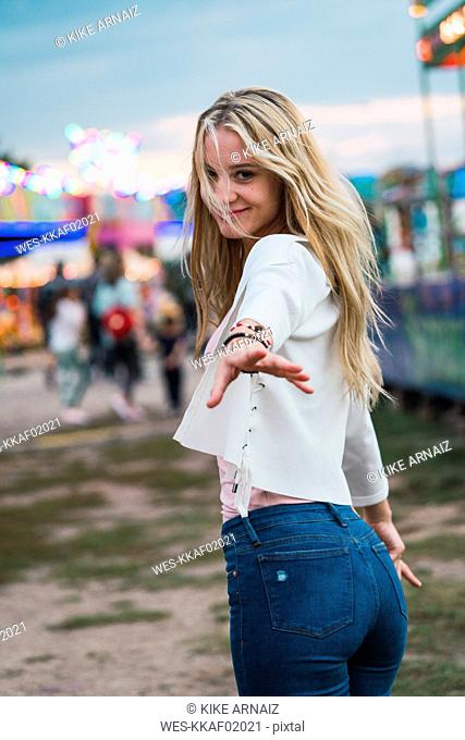 Smiling young woman on a funfair reaching out her hand
