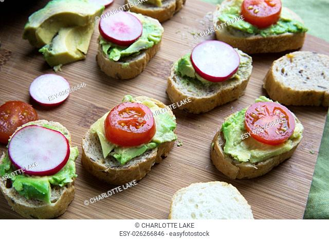 Healthy bites of avocado toast topped with tomato and radish slices