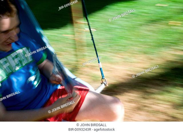 Teenage boy with Autism swinging in a tree