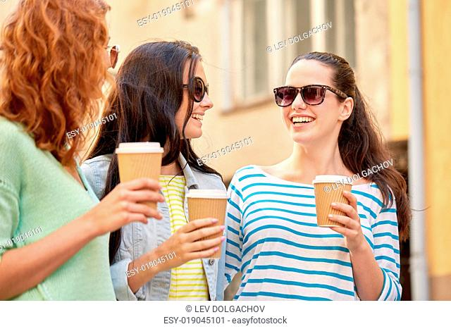 vacation, weekend, takeaway drinks, leisure and friendship concept - smiling happy young women or teenage girls drinking coffee from disposable paper cups on...