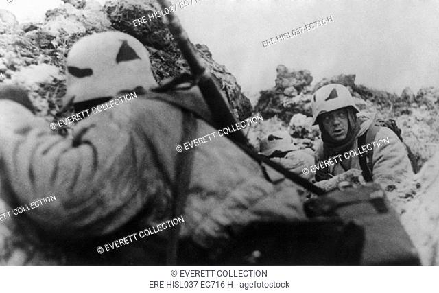 German soldiers crouching behind earthworks near Leningrad during Soviet (Russian) bombardment. Ca. 1943 during World War 2. (BSLOC-2014-8-38)