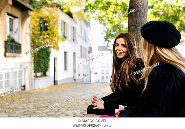 France, Paris, two young women sitting on a bench in the streets of Montmartre