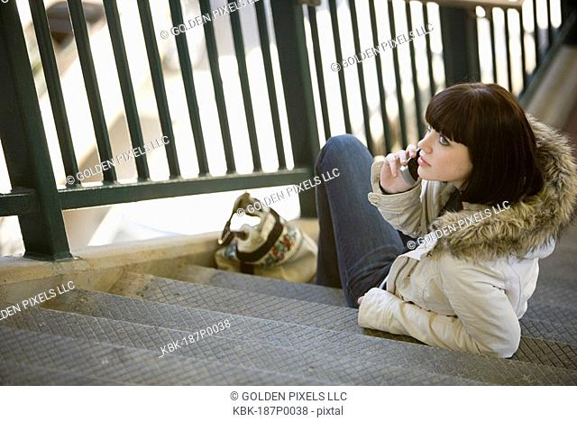 Elevated view of a young woman holding cellphone sitting on concrete steps