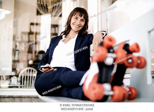 Businesswoman wearing roller skates, holding smartphone