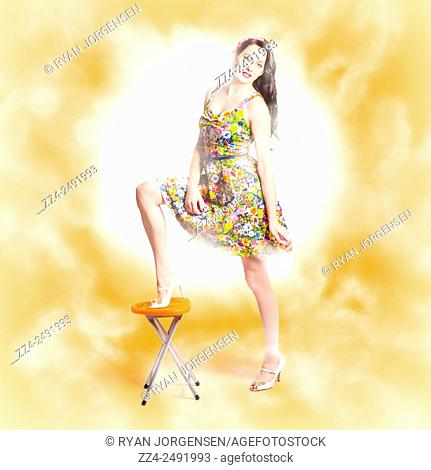 Vibrant beauty and fashion model standing on bar stool wearing floral dress with bright glam lights. Backlit pin-up beauty