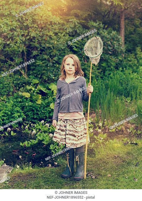 Girl standing in garden with bag net