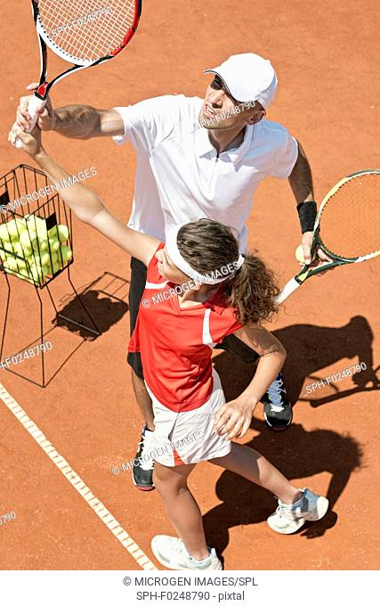 Coach with junior player in tennis class