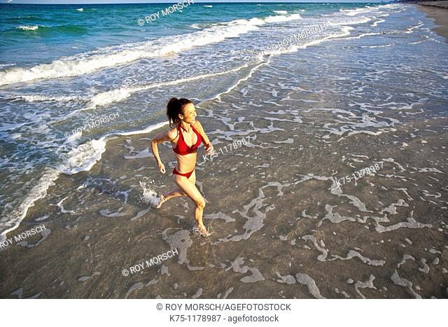 woman running in shallow water at beach