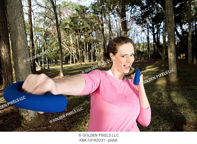 Portrait of a young woman exercising with hand weights in a park