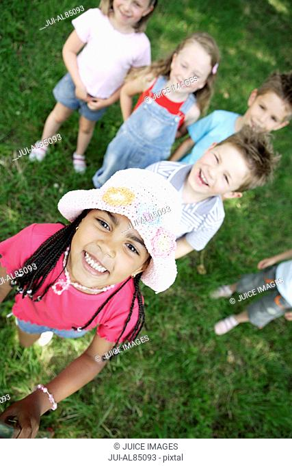 High angle view of group of young children smiling outdoors