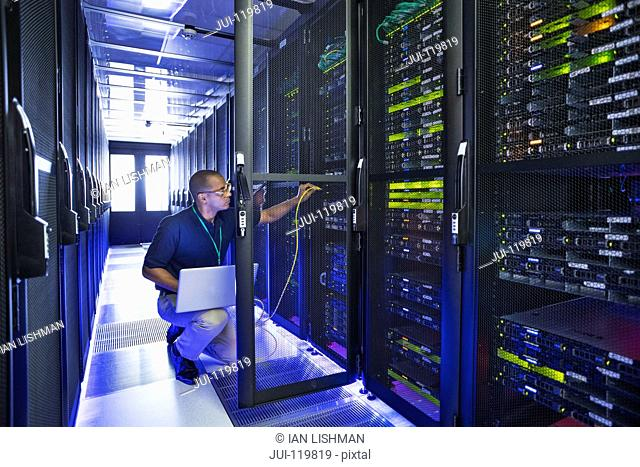 Technician with laptop working at mainframe computers in data center server farm