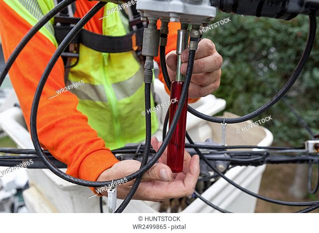 Cable lineman using nut driver to remove connection from a bucket truck
