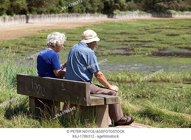 elderly man and woman sat on bench in the sunshine at Langston harbour at low tide with I Love you grafitti