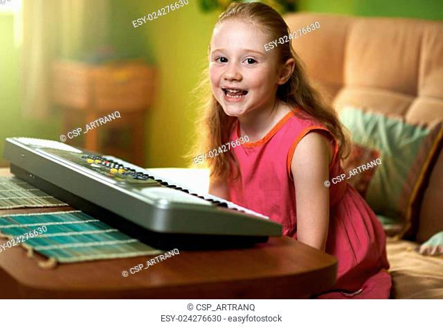 cheerful girl sits near electronic piano