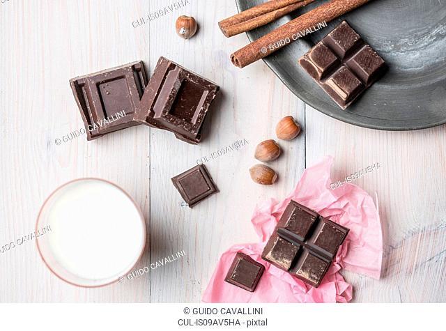 Overhead view of chocolate cubes, hazelnuts, cinnamon sticks, glass of milk