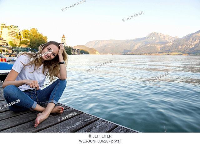 Austria, Sankt Wolfgang, smiling woman sitting on jetty at lake