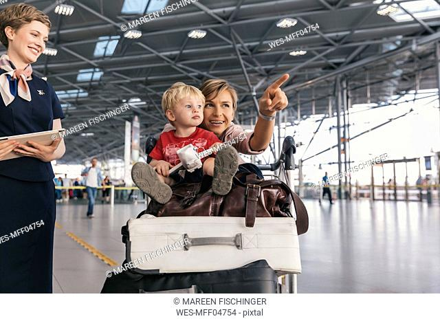 Travelling mother showing her young child around at the airport