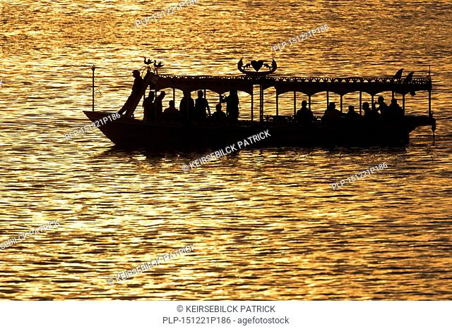 Silhouette of water taxi with tourists on the river Nile at sunset, Egypt