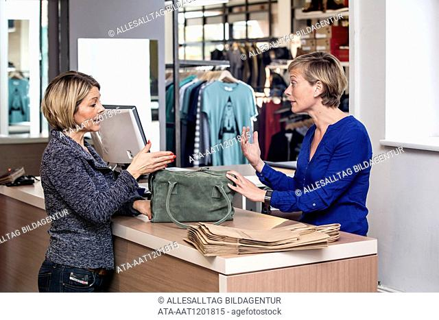 Woman is returning a handbag in a boutique
