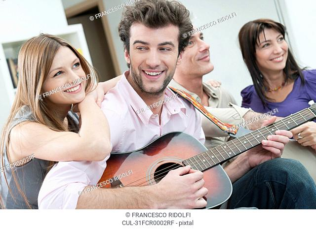Happy friends playing guitar together
