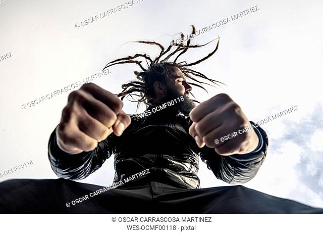 Bearded man with dreadlocks clenching fists