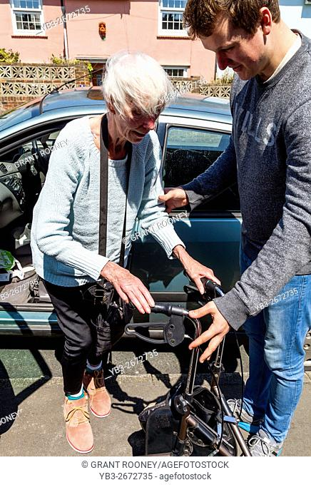 An Elderly Disabled Woman Getting Out Of A Car Helped By Her Grandson, Brighton, Sussex, UK