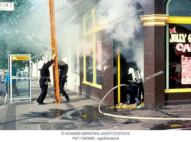 Firemen in action on a suburban North Melbourne street as two of them raise their ladder and the third enters the smoke filled doorway