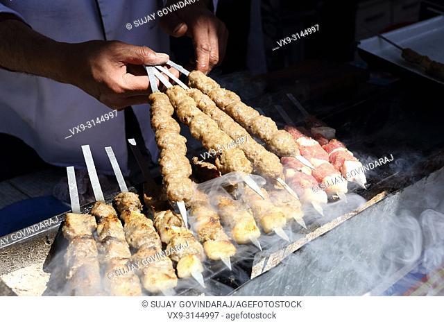 """Tashkent, Uzbekistan - May 01, 2017: Unknown Uzbek cook preparing """"""""Shashlik"""""""", a regional Uzbek food at food court"""