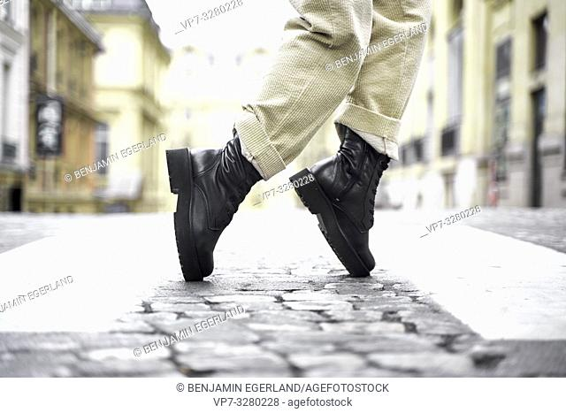 trendy black boots of fashionable woman at street during fashion week, in Paris, France