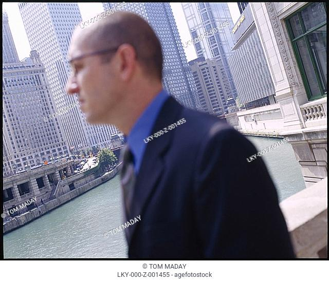 Profile of man against backdrop of Chicago River and the Loop