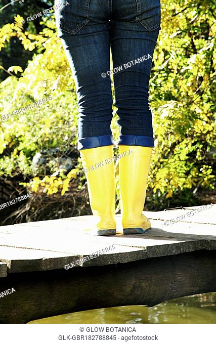 Low section view of a woman standing on a footbridge